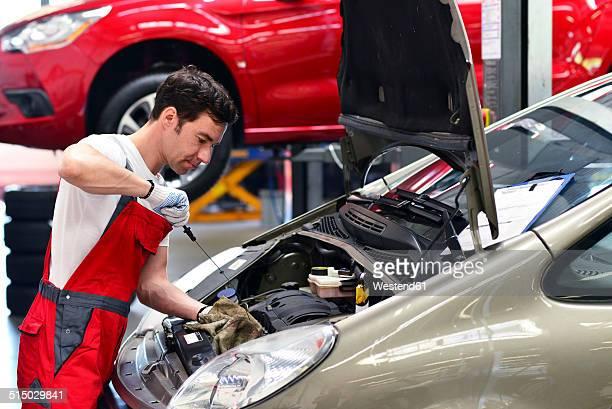 car mechanic in a workshop working at car - car lubricants 個照片及圖片檔