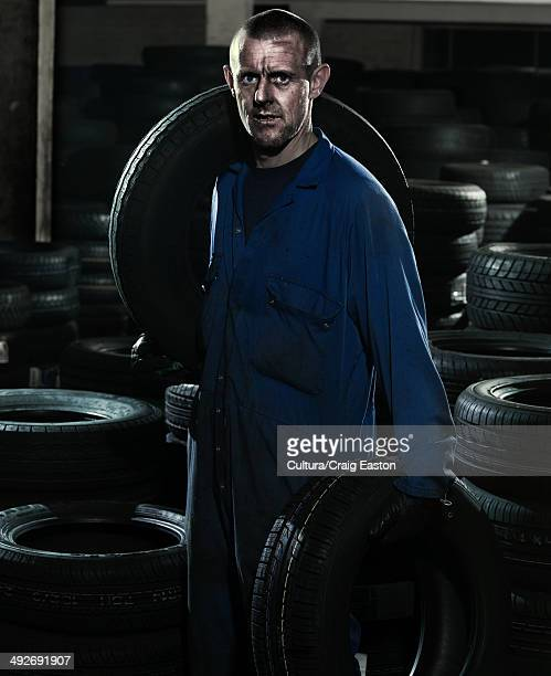 Car mechanic in workshop with car tires