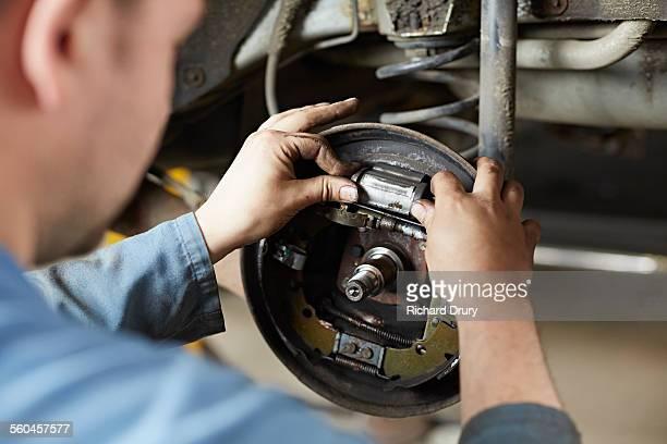 Car mechanic inspecting brakes