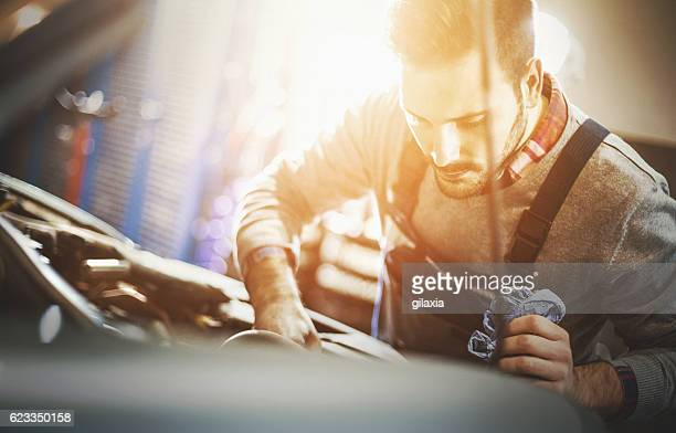 Car mechanic inspecting engine during service procedure.