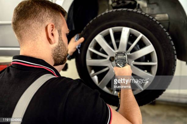 車のメカニックはタイヤを交換しています - 交代 ストックフォトと画像