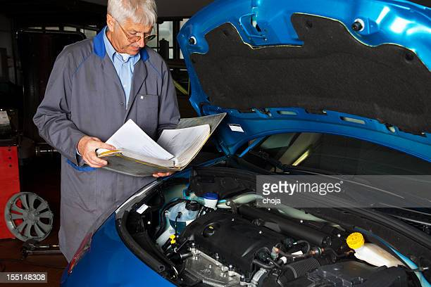 .Car mechanic is reading instruction manual of  car engine