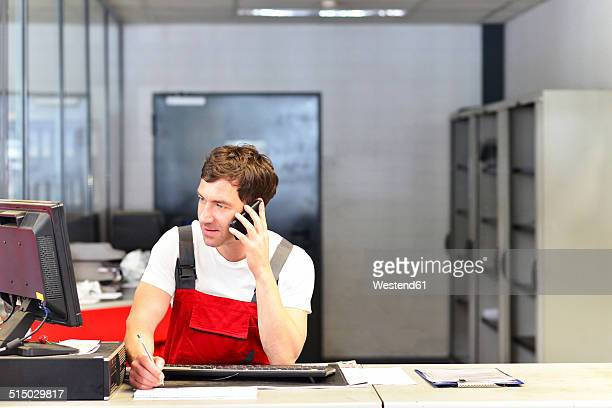 Car mechanic on the phone in service area of a car workshop