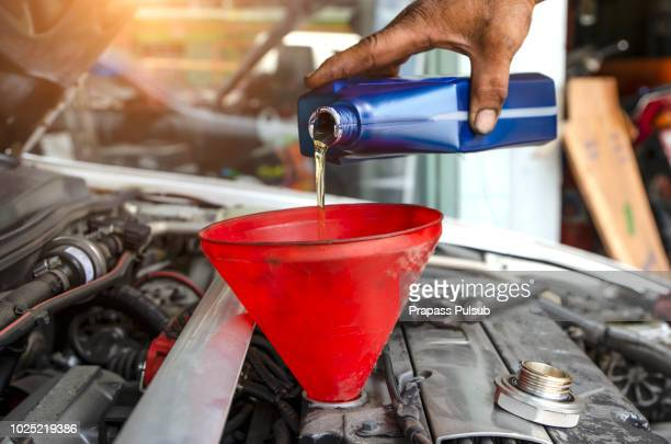 car mechanic replacing and pouring fresh oil into engine at maintenance repair service station - car lubricants 個照片及圖片檔