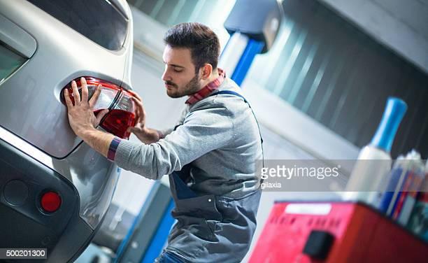 Car mechanic replacing tail light on a vehicle.