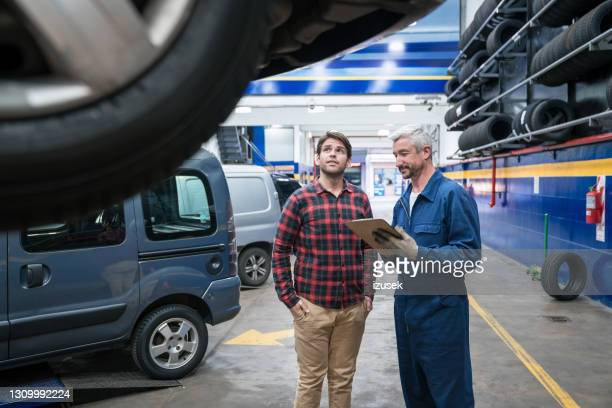 car mechanic talking with customer - izusek stock pictures, royalty-free photos & images