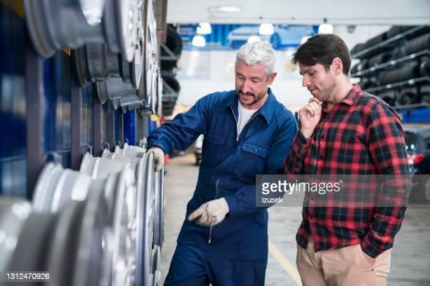 car mechanic talking with customer - izusek imagens e fotografias de stock