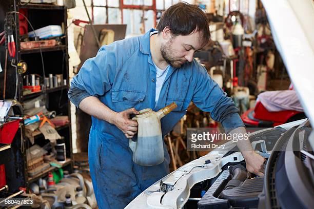 Car mechanic topping up fluid