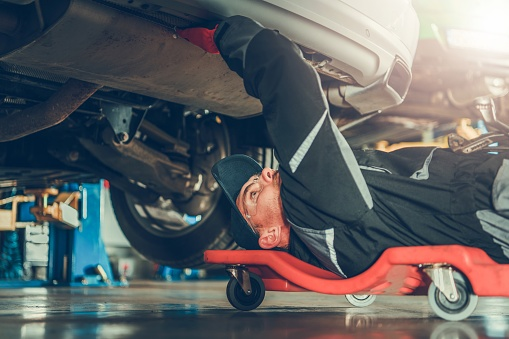 Car Mechanic Under the Car 1058126504