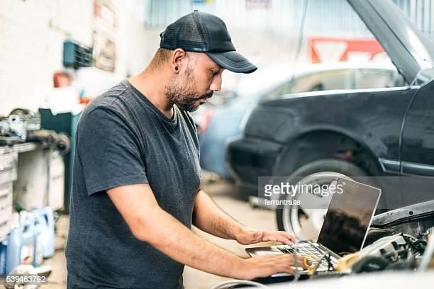 Mécanicien à l'aide d'ordinateur dans la voiture auto réparation boutique
