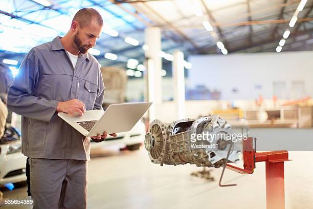 Car mechanic using laptop in repair garage