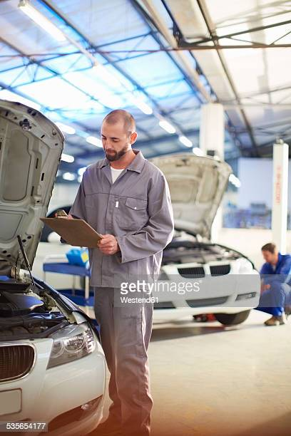 Car mechanic with clipboard in repair garage