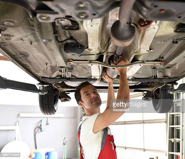 Car mechanic working in repair garage, checking underbody of a car