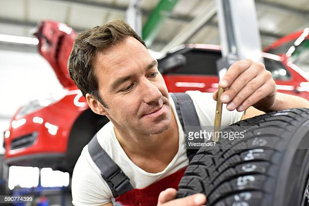 Car mechanic working in repair garage, controlling of pattern depth