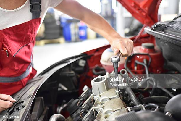 Car mechanic working in repair garage, dismantling cylinder head