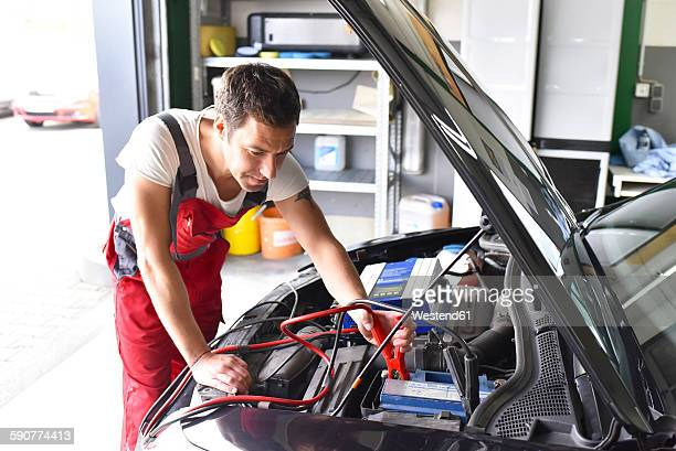 Car mechanic working in repair garage, reloading car battery