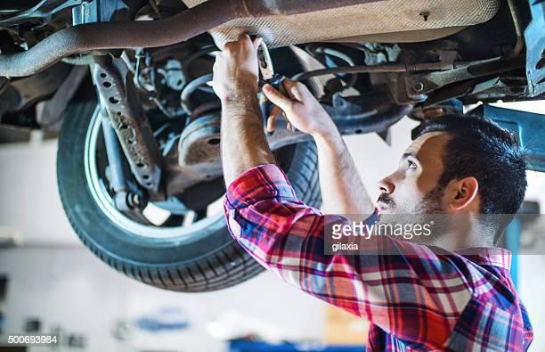 Auto-Mechaniker Arbeiten unter ein Auto in der Werkstatt.