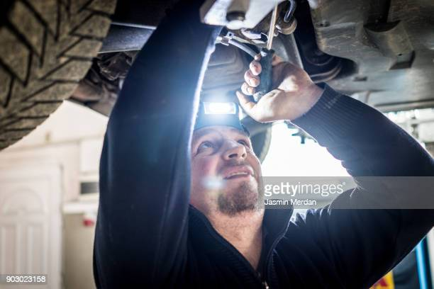 Car mechanic working under a vehicle at workshop