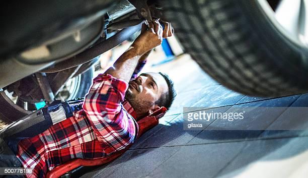 Auto-Mechaniker Arbeiten unter ein Auto.
