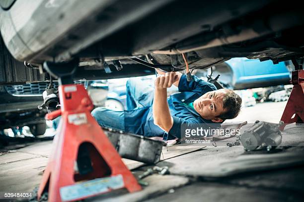 Car Mechanic Working Under Vehicle