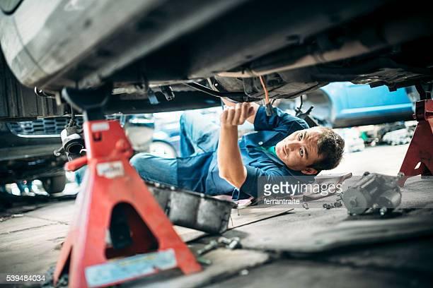Mécanicien travaillant sous voiture du véhicule