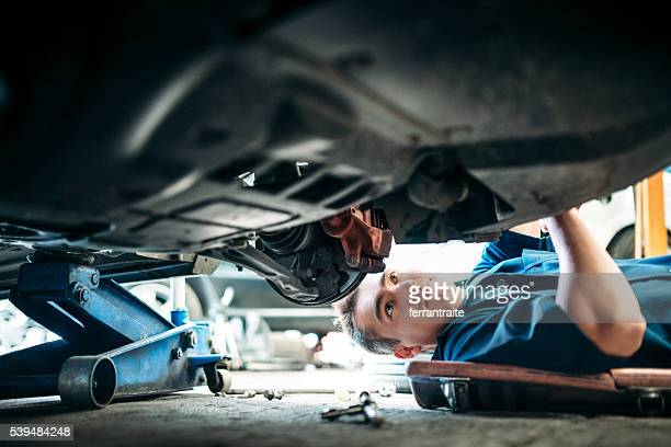 car mechanic working under vehicle - auto repair shop stock pictures, royalty-free photos & images