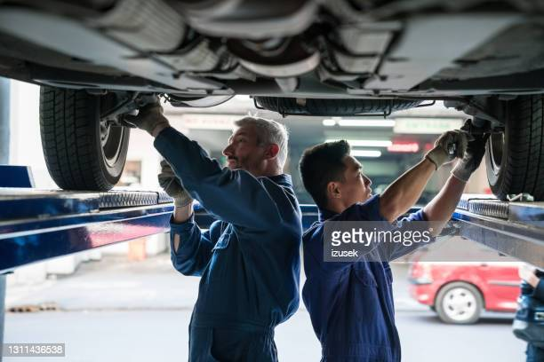 car mechanics checking vehicle chassis - mature adult stock pictures, royalty-free photos & images