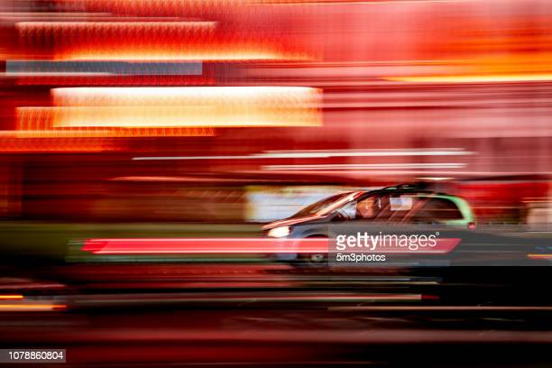 car motion blur on city street at night - bewegungsunschärfe stock-fotos und bilder