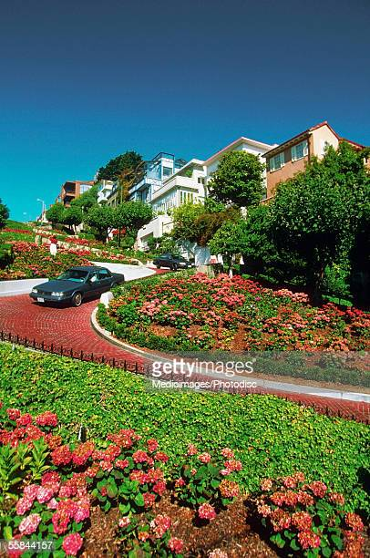 car moving down the street, lombard street, san francisco, california, usa - lombard street san francisco stock pictures, royalty-free photos & images