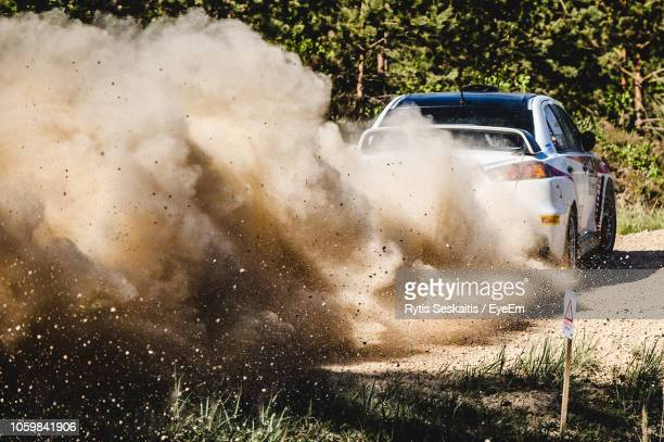 car moving on dirt road - dust stock pictures, royalty-free photos & images