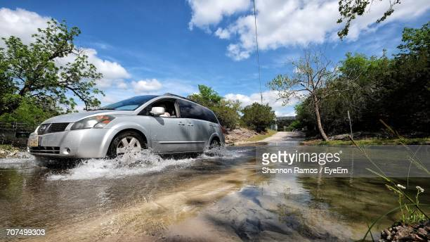 Car Moving On Flooded Road Against Sky