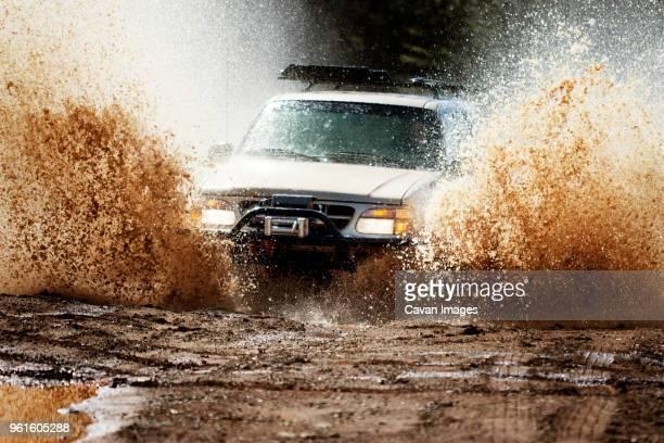 car moving on muddy road - schlamm stock-fotos und bilder