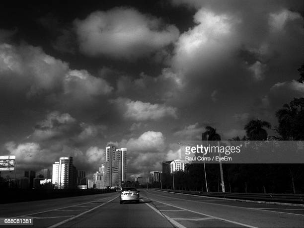 Car Moving On Road Against Cloudy Sky