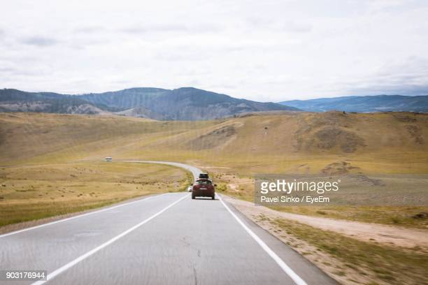 Car Moving On Road Against Mountains