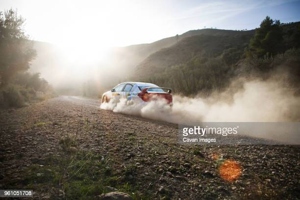 car moving on road against sky on sunny day - dust stock pictures, royalty-free photos & images