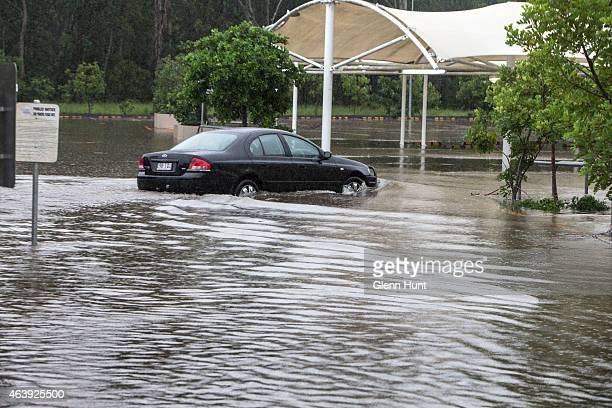 A car navigates flooding in a Burpengary shopping centre carpark on February 20 2015 in Brisbane Australia Brisbane and the Gold Coast are...