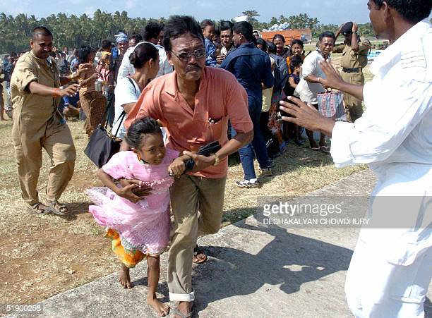Car Nicobar residents rush towards an Indian army airplane to be evacuated from the tsunamihit island 29 December 2004 The death toll in the tidal...