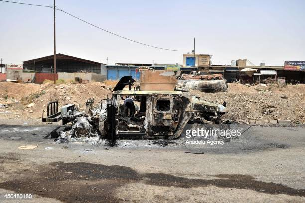 Car of Iraq army is burned by militants of Islamic state of Iraq and the Levant on the outskirts of Mosul, in Iraq on 12 June, 2014.