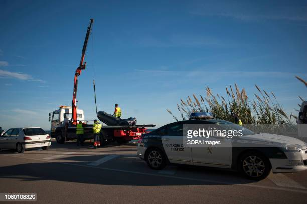 A car of Spanish Civil Guards seen taking custody of the dinghy after arriving on the beach with a group of migrants A dinghy with migrants and two...