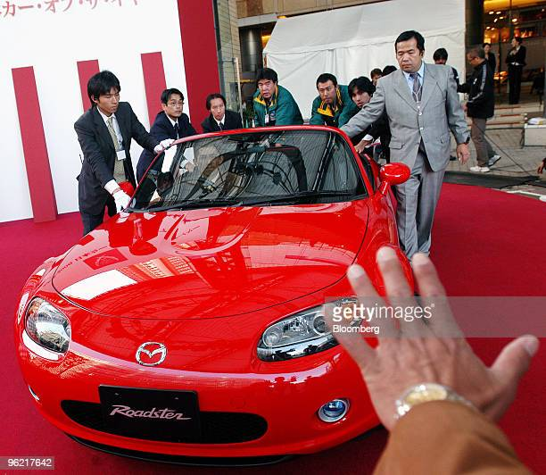 Car of the Year Awards staff push a Mazda Motor Corp Roadster voted Japan's Car of the Year 20052006 on to the winner's red carpet towards gesturing...