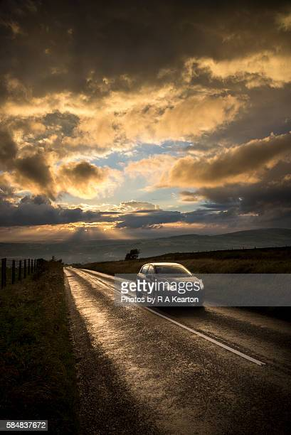 Car on a hillside road at sunset