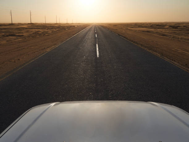 Car on a tarmac road in the desert at sunset, Solitaire area, Namibia