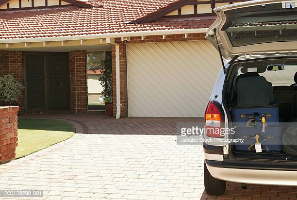 car on driveway, suitcases in open boot - mini van stock photos and pictures