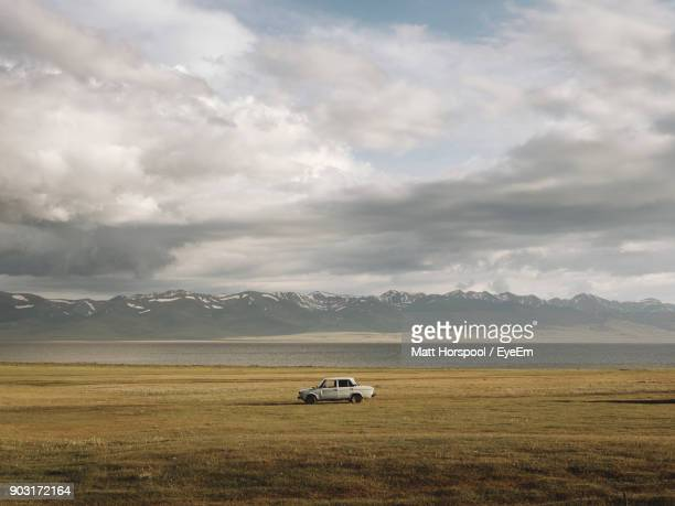 car on field against cloudy sky - kyrgyzstan stock pictures, royalty-free photos & images