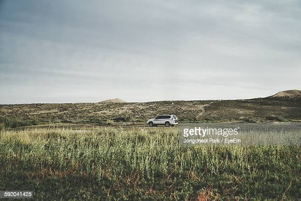 Car On Grassy Field Against Cloudy Sky