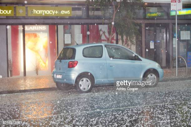 car on hail covered street during a tropical storm in melbourne, australia - hail damage car stock pictures, royalty-free photos & images