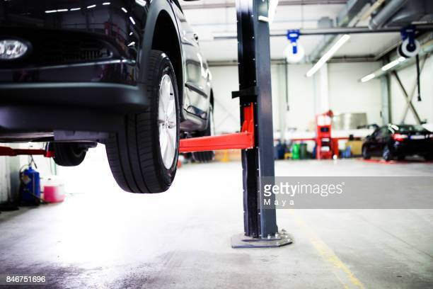 car on lift at car service - sollevare foto e immagini stock