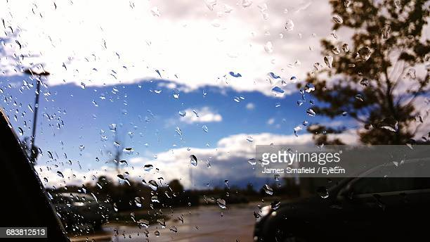 Car On Road Against Cloudy Sky Seen From Wet Windshield During Rainy Season