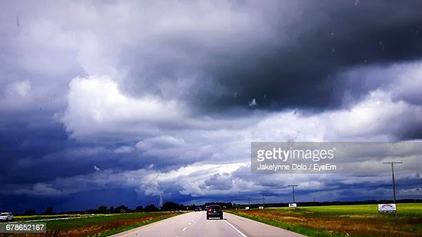Car On Road Amidst Field Against Storm Clouds