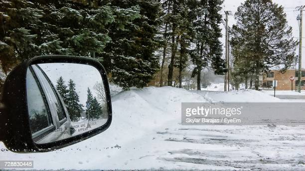 Car On Snow Covered Road Against Trees